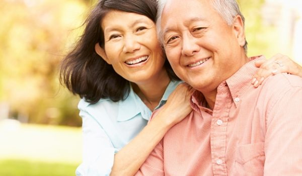 Portrait Of Senior Asian Couple Sitting In Park Together